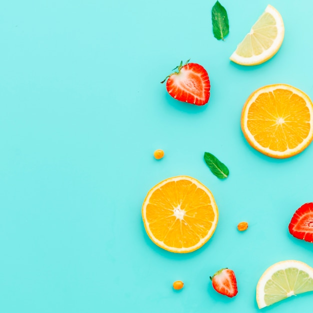 Sliced citrus fruits and strawberry on table Free Photo