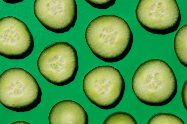 Sliced cucumber pattern on a green background Free Photo