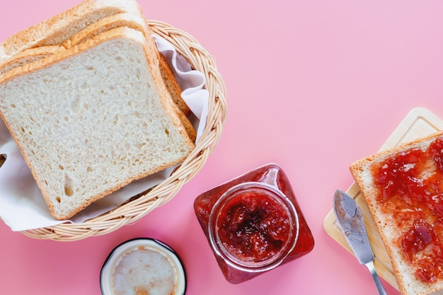 Sliced fine whole wheat bread with strawberry spread on pink background Premium Photo