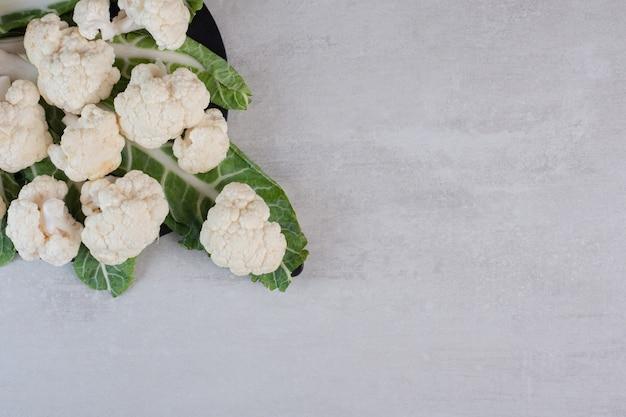 Sliced fresh cauliflower with leaves on black board. high quality photo Free Photo