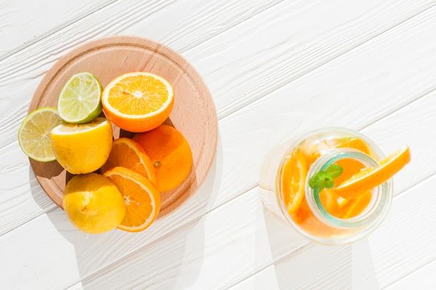Sliced fruit with bottle of lemonade Free Photo
