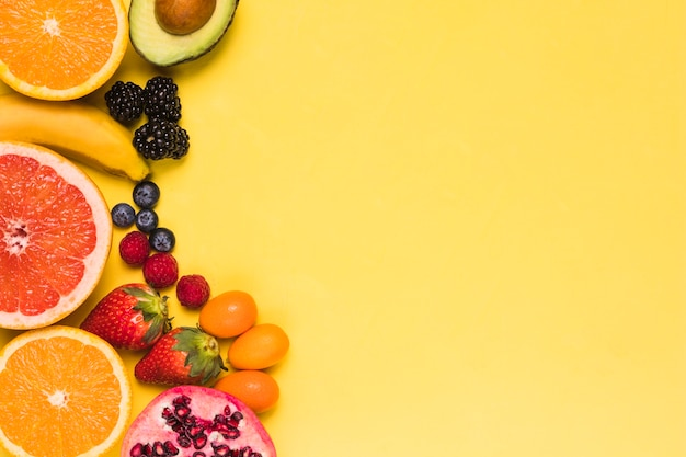 Sliced fruits and berries on yellow background Free Photo