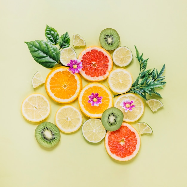 Sliced fruits decorated with leaves and flowers Free Photo