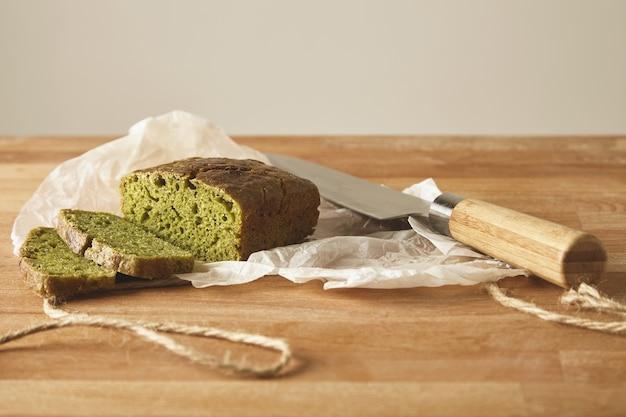 木の板を切る上でアンティックナイフで分離されたほうれん草生地からスライスされた緑の素朴な健康的なパン 無料写真
