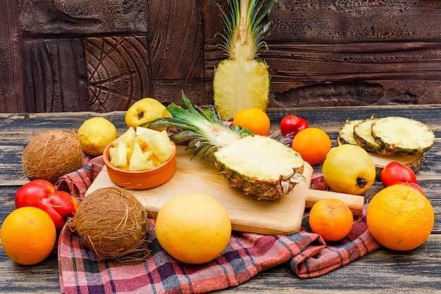 Нарезанные сочные ананасы с кокосами, персиками, айвой и цитрусовыми фруктами в деревянные доски и миску на деревянной поверхности гранж, ткань для пикника и каменная плитка, плоская планировка. Бесплатные Фотографии