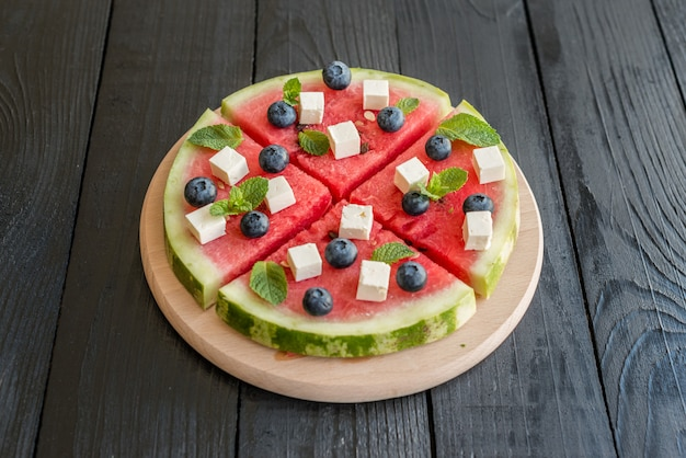 Sliced, juicy watermelon pizza with blueberries and cheese Premium Photo