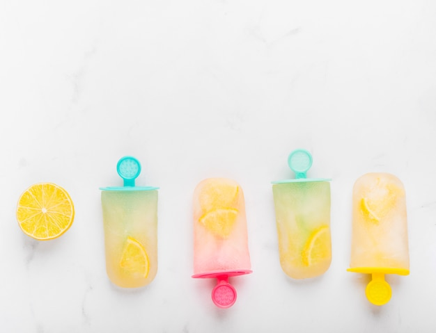 Sliced lemon and fresh ice popsicle with citrus on colorful sticks Free Photo