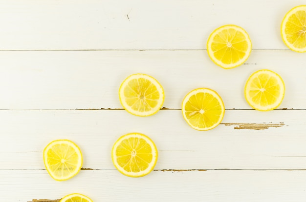 Sliced lemons scattered on table Free Photo