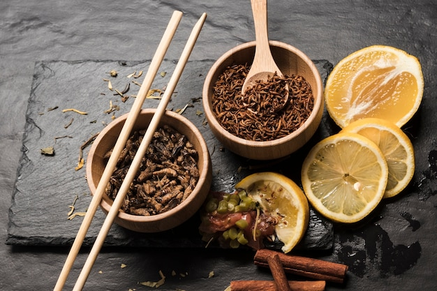 Sliced lemons with wooden bowls filled with insects Free Photo