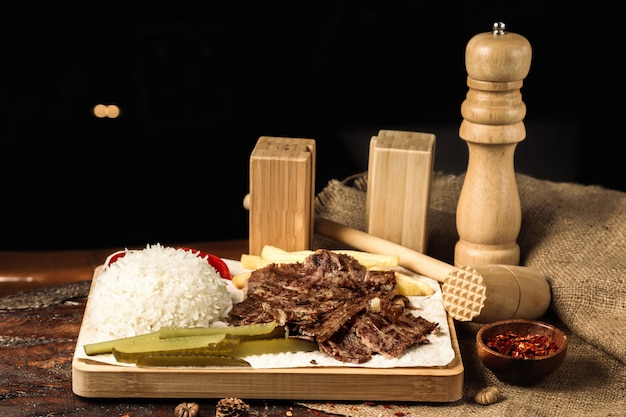 Sliced meat with boiled rice and slices of pickles Free Photo