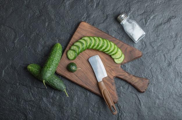 塩とナイフで木の板にスライスまたは丸ごとキュウリ。高品質の写真 無料写真