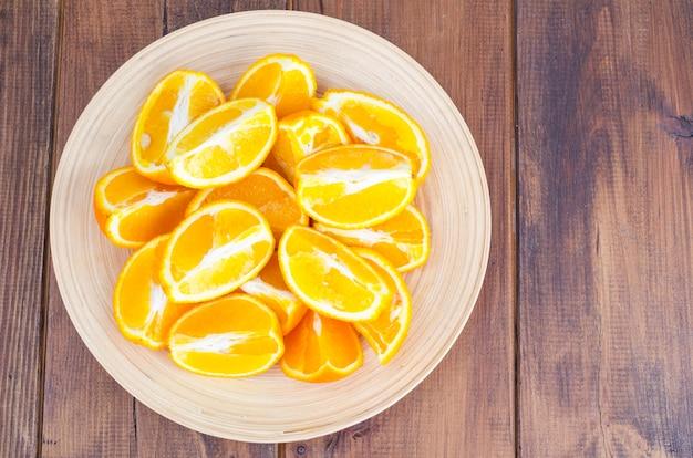 Sliced orange slices on wooden plate. Premium Photo