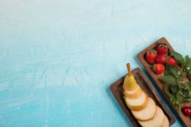 Нарезанные груши с клубникой и другими ягодами на деревянных тарелках в углу Бесплатные Фотографии