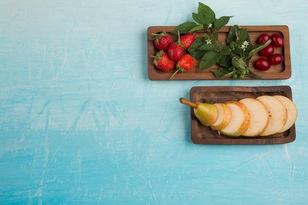 Нарезанные груши с клубникой на деревянных тарелках, вид сверху Бесплатные Фотографии