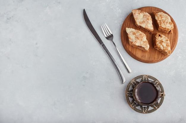 お茶のグラスと木製の大皿にスライスしたパイ、上面図。 無料写真