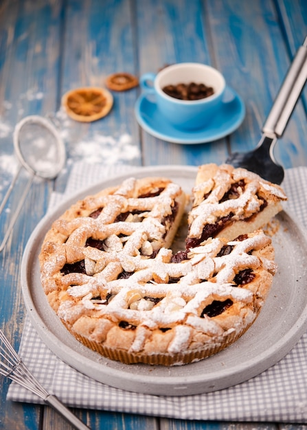 Sliced pie with dried citrus and sieve Free Photo