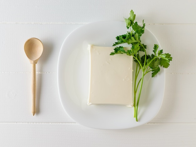 Sliced piece of serbian cheese with parsley on a plate. Premium Photo