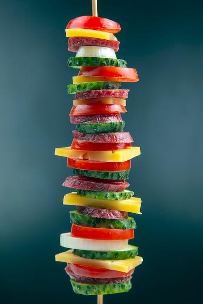 ソーセージ、サラミ、チーズ、きゅうり、トマトのスライス。ファストフード。ピザの材料。カロリーと食事 Premium写真