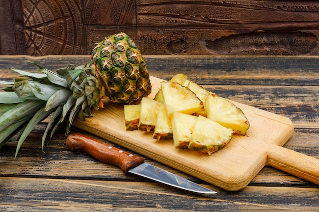 Sliced pineapple in a cutting board with a fruit knife side view on a wood grunge surface and stone tile Free Photo