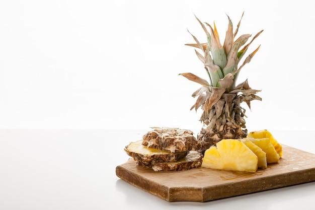 Нарезанные ломтики ананаса на кухонной доске Premium Фотографии