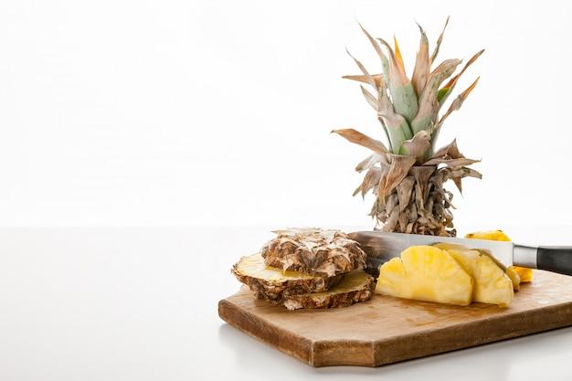 Ломтики ананаса с ножом на кухонной доске Premium Фотографии