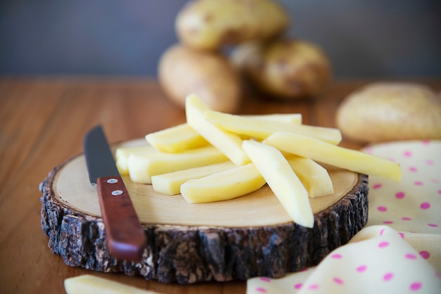 Sliced potato stick ready for making french fries - traditional food preparation concept Free Photo
