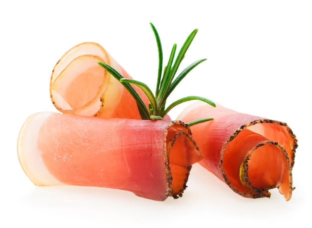 Sliced prosciutto with rosemary on white background Premium Photo