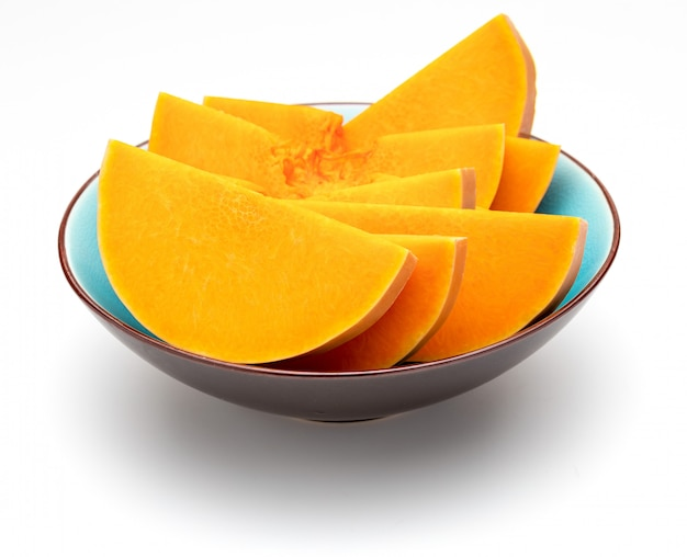 Sliced pumpkin in blue bowl. isolated Premium Photo