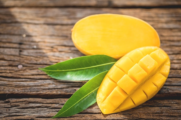 Sliced ripe mango on wooded board with green leaves. Premium Photo