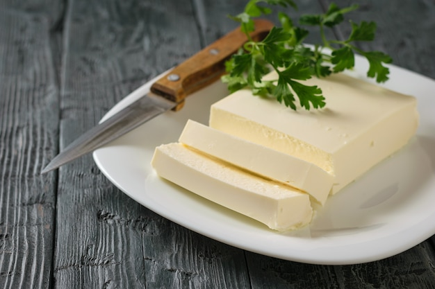 Sliced serbian cheese with a knife and parsley leaves on a black wooden table. Premium Photo