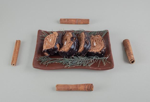 Rotolo di cioccolato dolce a fette con bastoncini di cannella. Foto Gratuite
