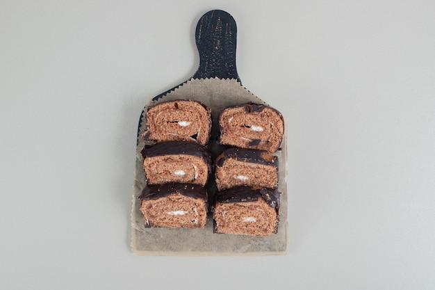 Rotolo di cioccolato dolce a fette su una tavola di legno. Foto Gratuite