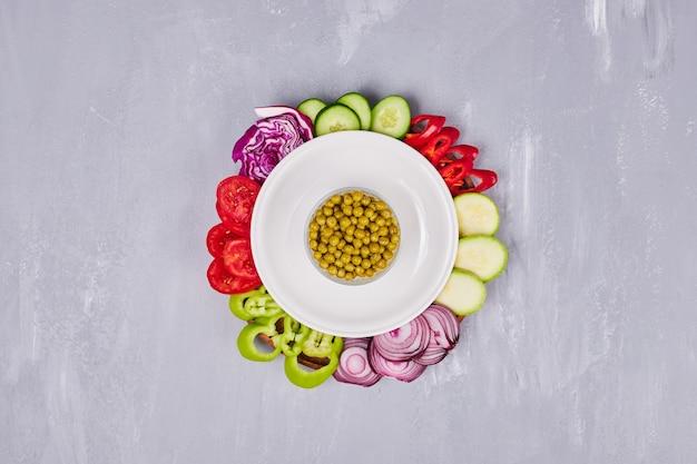 Verdure ed erbe a fette in un piatto bianco, vista dall'alto. Foto Gratuite