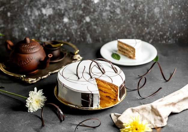 Sliced white glazed cake decorated with chocolate pieces Free Photo