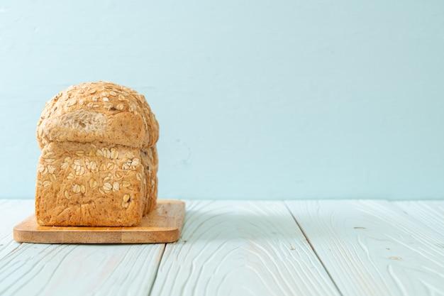 木製のテーブルで全粒パンをスライス Premium写真