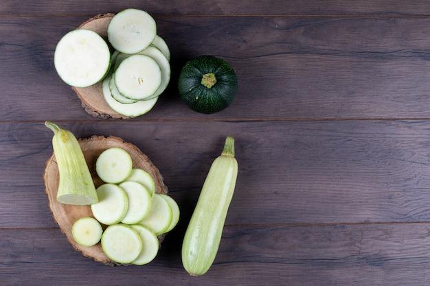 Zucchine a fette su tronconi e tavolo in legno scuro. vista dall'alto Foto Gratuite
