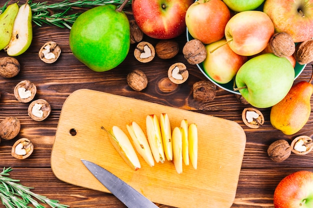 Slices of apple on chopping board with fruits and walnuts over the table Free Photo