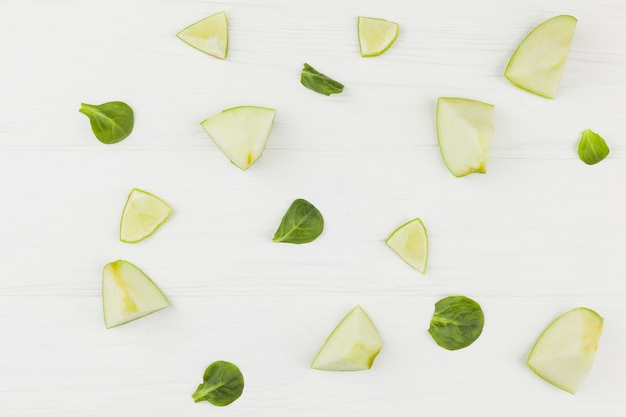Slices of apples lime and green leaves on a white background Free Photo