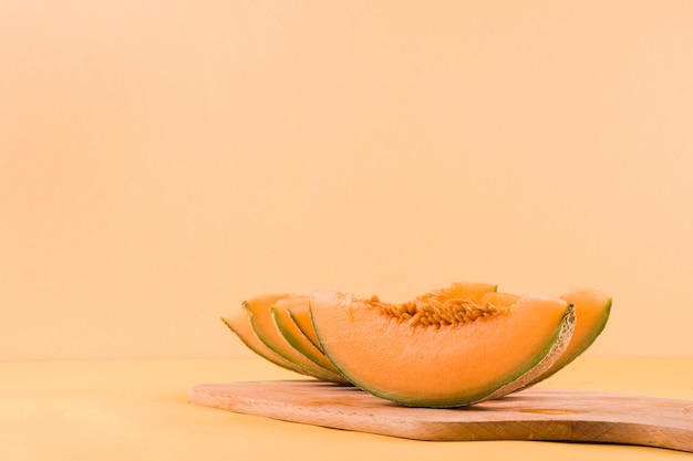 Slices of cantaloupe fruits on chopping board against colored backdrop Free Photo