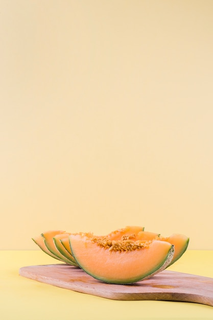 Slices of cantaloupe on wooden chopping board against beige backdrop Free Photo