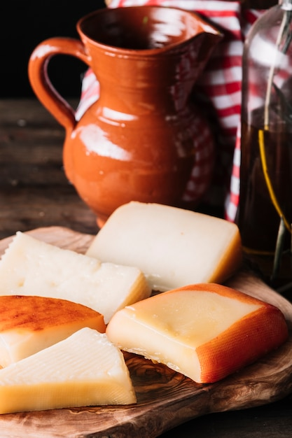 Slices of cheese near jug and oil Free Photo