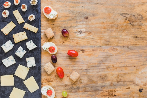 Slices of cheese; tomatoes and grapes on wooden surface Free Photo
