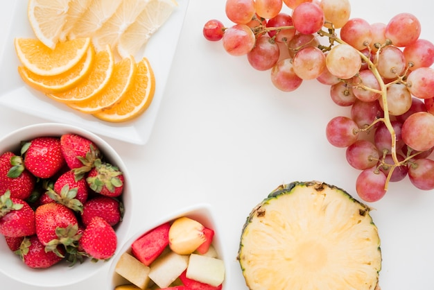 Slices of citrus fruit; strawberry; pineapple; watermelon and grapes on white backdrop Free Photo