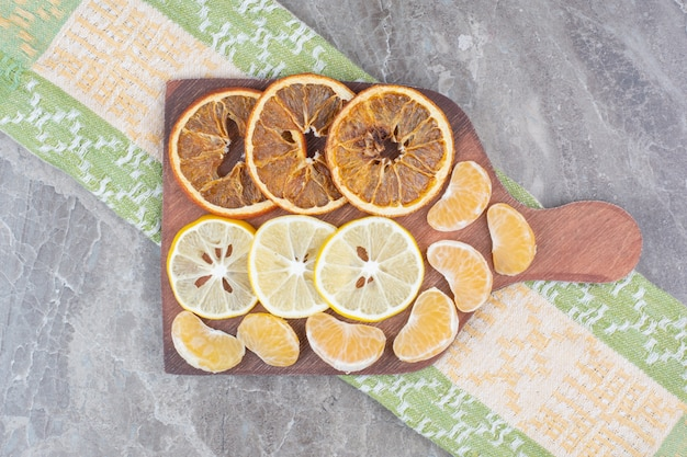 Slices of citrus fruits on wooden board with tablecloth. Free Photo