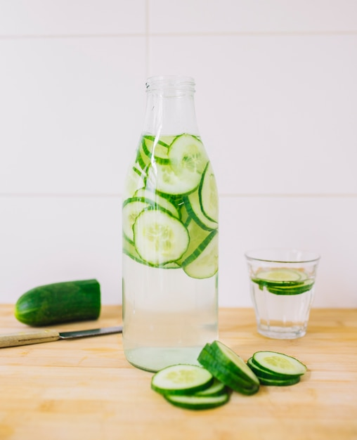 Slices of cucumber in the bottle of water and glass on wooden desk against wall Free Photo