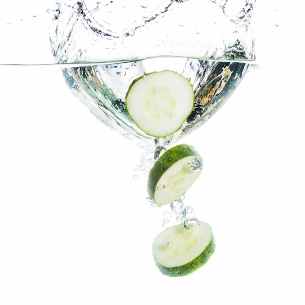Slices of cucumber falling into water Free Photo