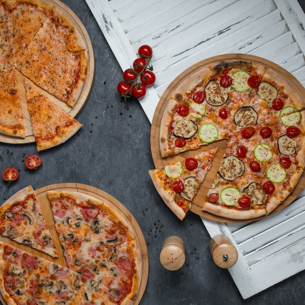 Slices cut from three varieties of pizzas Free Photo
