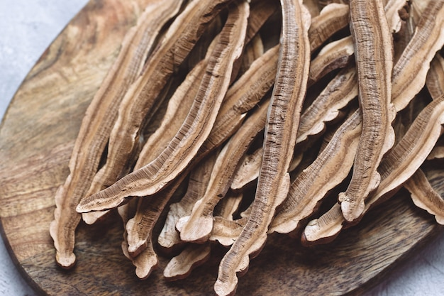 Slices of dried lingzhi mushroom, also called reishi, on a wooden board Premium Photo