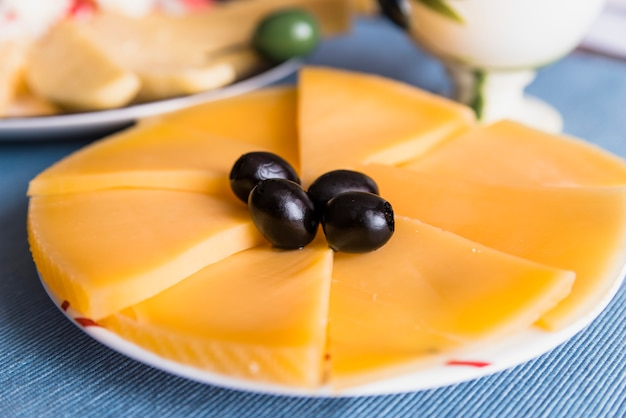 Slices of fresh cheese with tasty olives on plate Free Photo