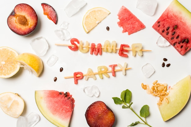 Slices of fruits between ice and summer party title Free Photo
